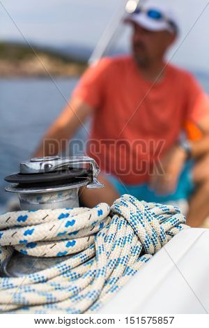 Rope on the yacht, a sailor is blurred in the background.