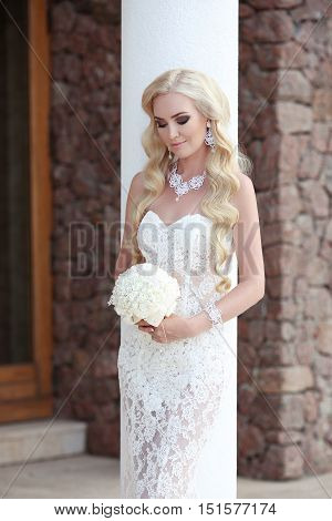 Beautiful Bride Wedding Portrait Holding Bouquet Posing In Lace Mermaid Dress. Makeup. Wavy Hairstyl