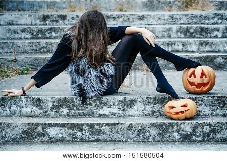 young halloween woman or girl witch with long hair in black tights and fur waistcoat sitting on stony stairs with traditional autumn holiday symbol of orange spooky pumpkin outdoor