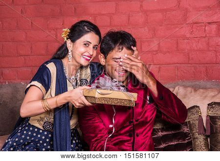 Indian wife surprising husband with a gift on diwali or anniversary or birthday, surprise gift concept and indian people or couple