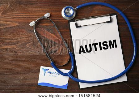 Children autism concept. Clipboard and stethoscope on wooden background