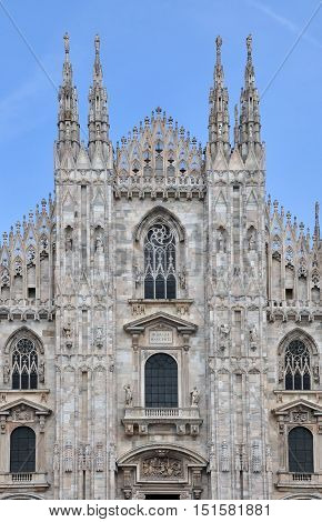 The front facade of the Duomo gothic cathedral in Milan with decorative elements sculptures and arched windows.
