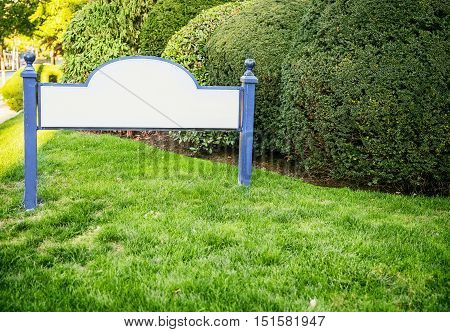 framed entrance sign with empty space for text. welcome blank sign in grass. the concept of houses and property for sale. mock up