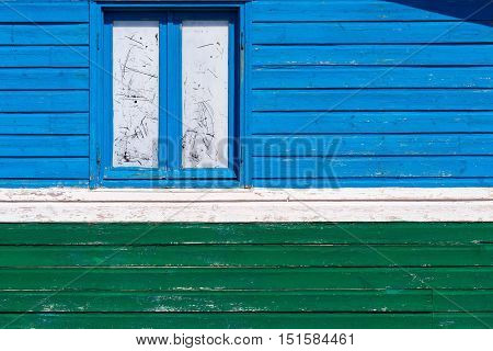 color fragment of an old wall of the house from wooden boards with one big window