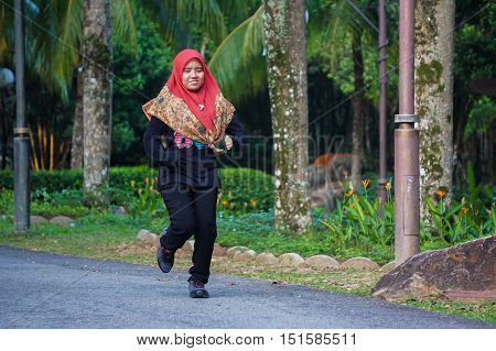 Labuan,Malaysia-Oct 13,2016:Young muslim woman runner running in Labuan Botanical Park,Labuan,Malaysia. Active lifestyle enthusiasts concept