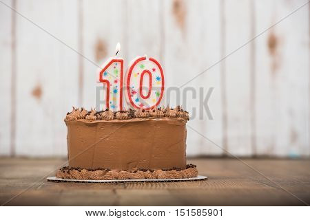 Chocolate frosted cake with wood background and table with ten candle