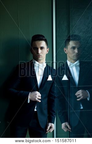 Man in suit with white handkerchief and bow tie young elegant stylish stands with plush lips and reflects in mirror on grey background