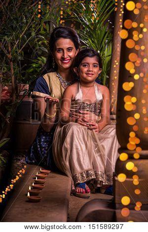 Portrait of indian mother and daughter with diyasor diya and lighting celebrating diwali or deepawali festival
