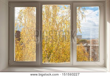 New white window overlook autumn yellow trees and clody sky