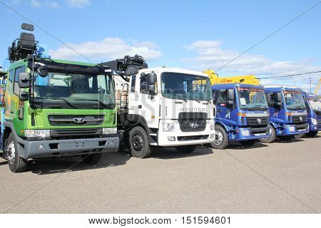 White blue green flatbed trucks with yellow crane arm is in the parking lot - Russia Moscow 30 August 2016