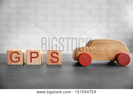 Cubes with abbreviation GPS and toy car on brick wall background