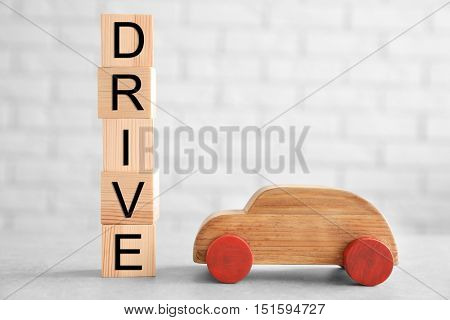 Cubes with word DRIVE and toy car on brick wall background