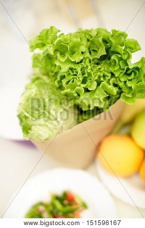 paper bag with fresh lettuce and cabbage, close-up