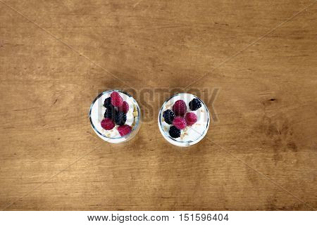 Yogurt parfait on a wooden table. Top view