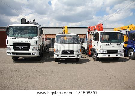 White Flatbed Trucks With Cranes Arm Is In The Parking Lot - Russia, Moscow, 30 August 2016
