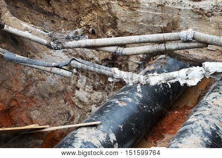 Repair Of Heating Duct. Large Iron Pipes At A Depth Of Excavated Trench.