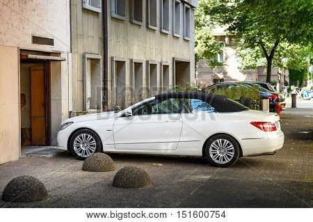 STRASBOURG FRANCE - JUL 4 2016: Luxury Mercedes-Benz CLK convertible car entering through garage door in modern calm city