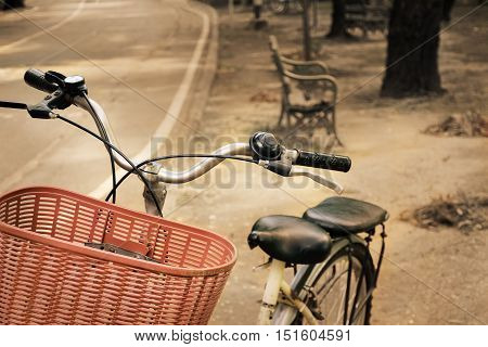 Close up of bicycle with blurry focus background of view beside road in park. shallow depth of field. Vintage effect tone.