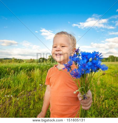 Adorable boy with cornflowers outdoor laughing