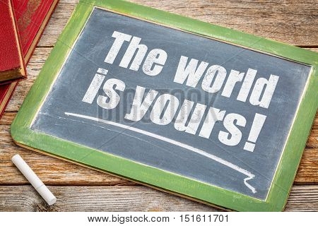 The world is yours - a positive affirmation. White chalk text on a blackboard with books.