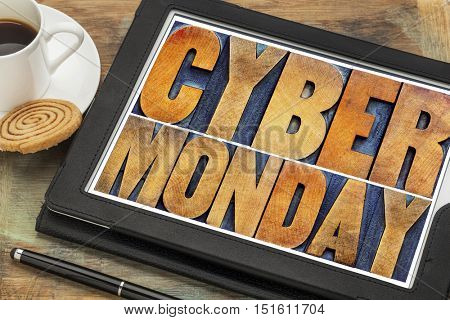 Cyber Monday - online shopping and marketing concept - word abstract in letterpress wood type printing blocks on a digital tablet with a cup of coffee