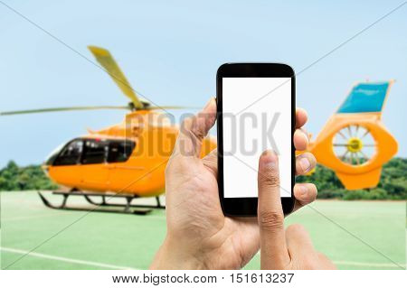 Hand holding smartphone with index finger touching the screen on the phone to rent the helicopter