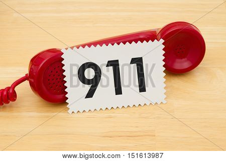 Calling to get help A retro red phone with note card on a desk with text 911