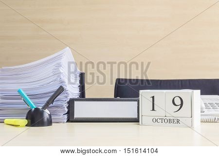 Closeup white wooden calendar with black 19 october word on blurred brown wood desk and wood wall textured background in office room view with copy space selective focus at the calendar