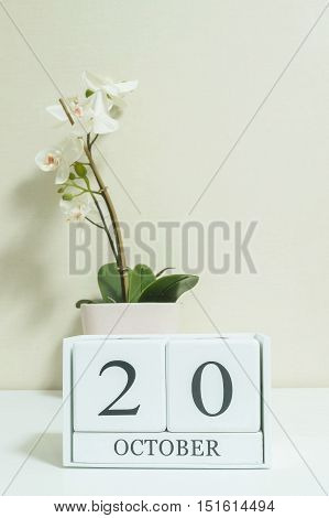 Closeup white wooden calendar with black 20 october word with white orchid flower on white wood desk and cream color wallpaper in room textured background selective focus at the calendar