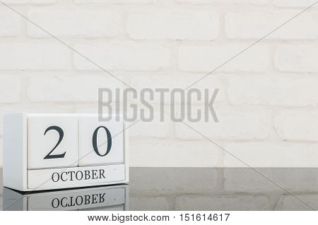 Closeup white wooden calendar with black 20 october word on black glass table and white brick wall textured background with copy space selective focus at the calendar