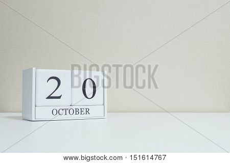 Closeup white wooden calendar with black 20 october word on blurred white wood desk and cream color wallpaper in room textured background with copy space selective focus at the calendar