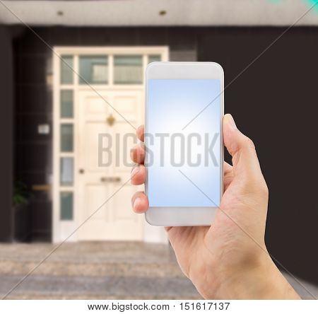 the hand holding the smartphone with house entry in the background like concept buy new house