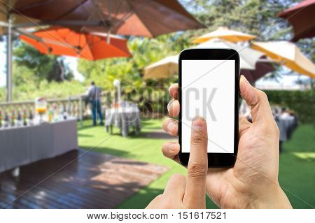 Hand holding smartphone with index finger touching the screen on the