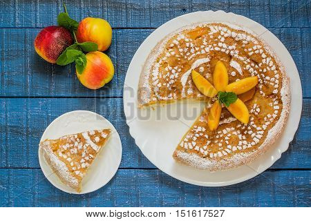 Delicious homemade cake with nectarines on a blue wooden table. Top view
