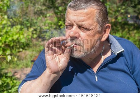 Portrait of Ukrainian senior peasant smoking cigarette rolled by himself with an old newspaper scrap and tobacco cultivated on an own garden