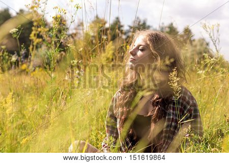 Beautiful young woman with closed eyes and long curly brown hair dressed in a check shirt is sitting on a meadow in high grass and gentle wild flowers