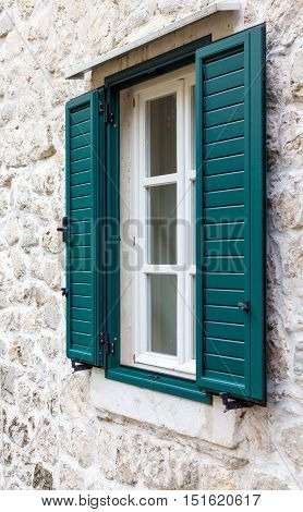 A Window In The Wall Of Stone With Open Green Shutters