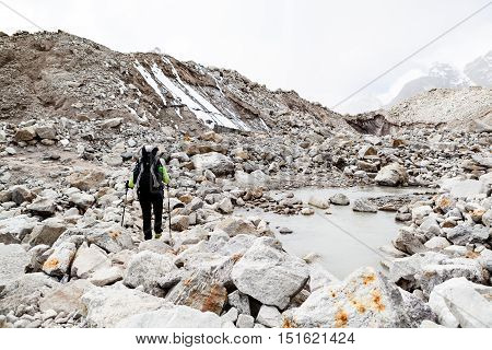 Woman hiker trekking with big backpack in Himalaya Mountains on Rocky Glacier Trail. Girl on hiking trail in high mountains travel and expedition in inspirational mountain landscapebeautiful views.
