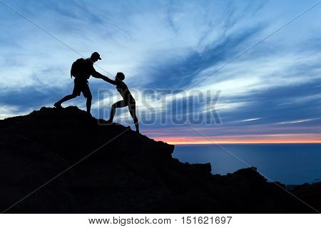 Teamwork couple hiking help each other trust assistance and silhouette in mountains sunset over ocean. Team of climbers man and woman helping hand on mountain top inspirational climbing team.
