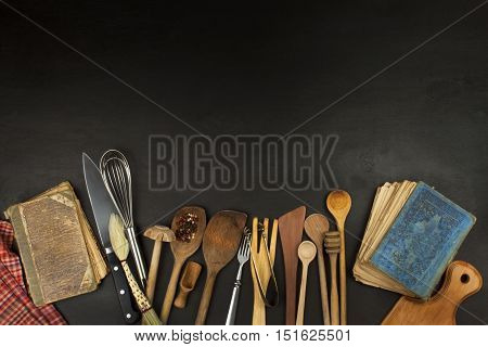 Kitchen utensils on wooden table. Tools cook. Needs to cook. Set of the wooden kitchen utensils on black wooden background.