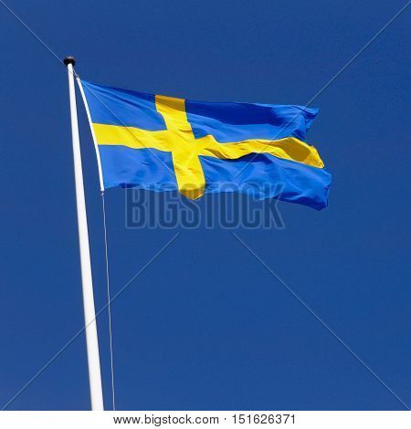 Swedish flag flies sunlit in the wind on a flagpole against a clear blue sky.