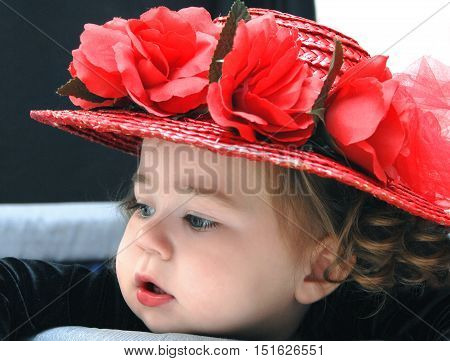 Beautiful baby girl is wearing a red straw hat with roses. Image is closeup and shows fat cheeks and sweet face.