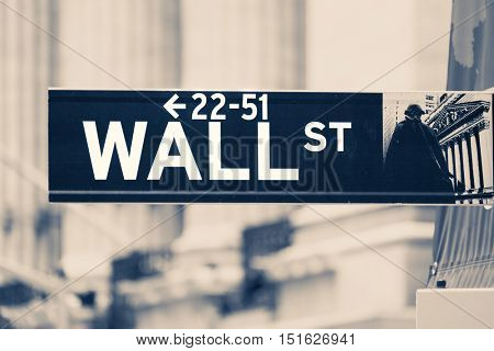 Vintage toned Wall Street sign next to the New York Stock Exchange