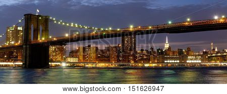 Panoramic image of the Brooklyn Bridge illuminated at night with reflections on the East River