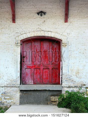Rustic red wooden door is framed by white painted bricks. Doorway is part of old train station in Stoughton Wisconsin.
