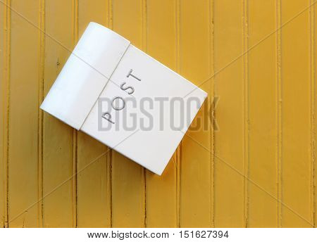 The white mailbox hanging awry on a yellow painted wooden wall.