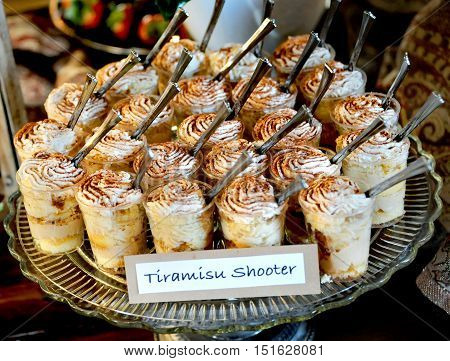 Wedding reception offers guests a Tiramisu Shooter. Plate holds group of desert glasses with spoons.