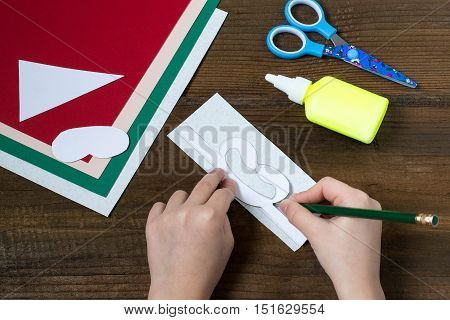 Creating a Christmas decoration for table setting. Decor for serviette in form of Santa Claus. Children project step by step photo instructions. Step 2. Drawing details by dint of templates