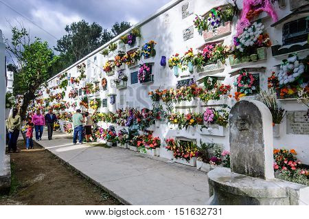 San Lazaro Cemetery Antigua Guatemala - November 2 2014: People decorate crypts of deceased family members with wreaths & flowers on All Souls' Day in Spanish colonial town of Antigua.