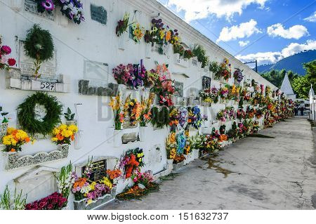San Lazaro Cemetery Antigua Guatemala - November 2 2014: Flowers & wreaths cover mausoleum on All Souls' Day in Spanish colonial town of Antigua.